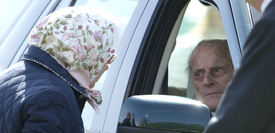 Queen Elizabeth II speaks to Prince Philip, Duke of Endinburgh through the car window at the third day of the Royal Windsor Horse Show