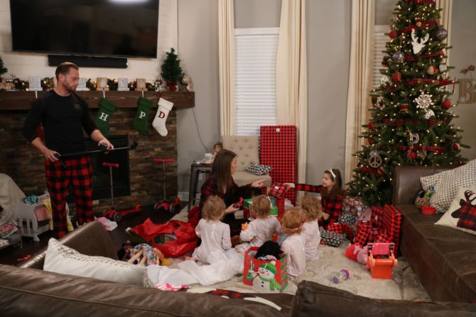 Adam, Danielle, Blayke Busby with the quints on Christmas morning opening gifts.