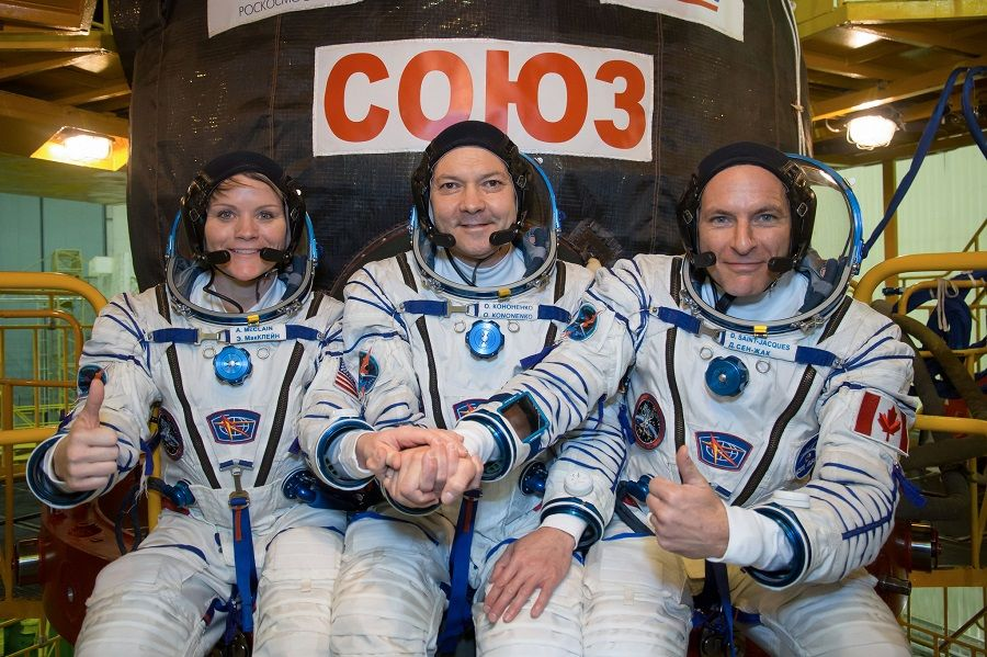 Expedition 58 crew members Anne McClain (left), Oleg Kononenko (center), and David Saint-Jacques (right) pose in front of their Soyuz MS-11 spacecraft.