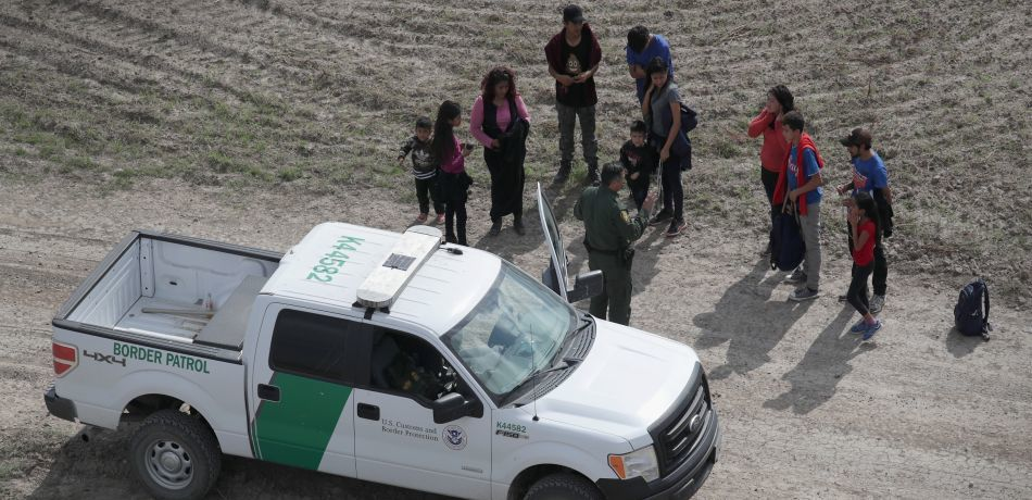 Border Patrol agents stop a group of migrants in the desert.