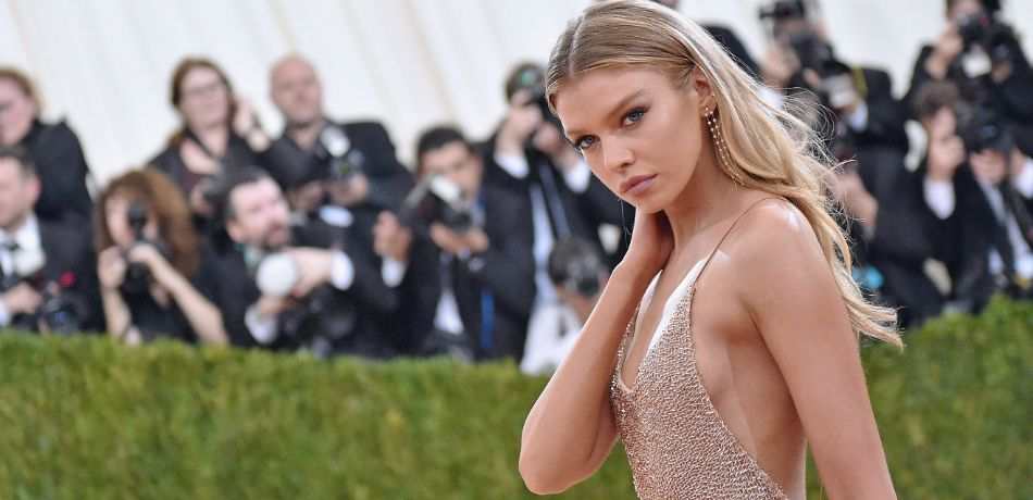 Stella Maxwell wears a skimpy dress and strikes a side pose