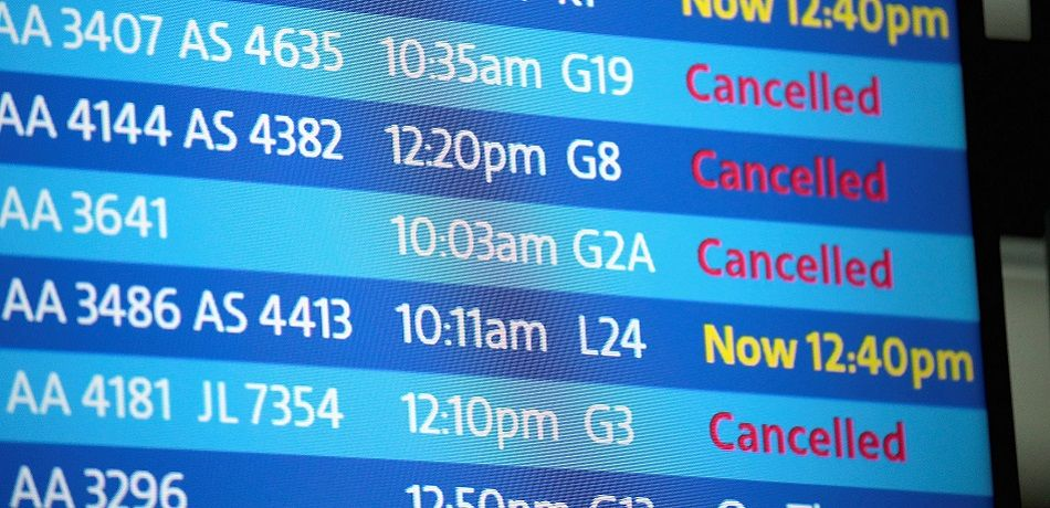 An electronic board shows flight delays and cancellations