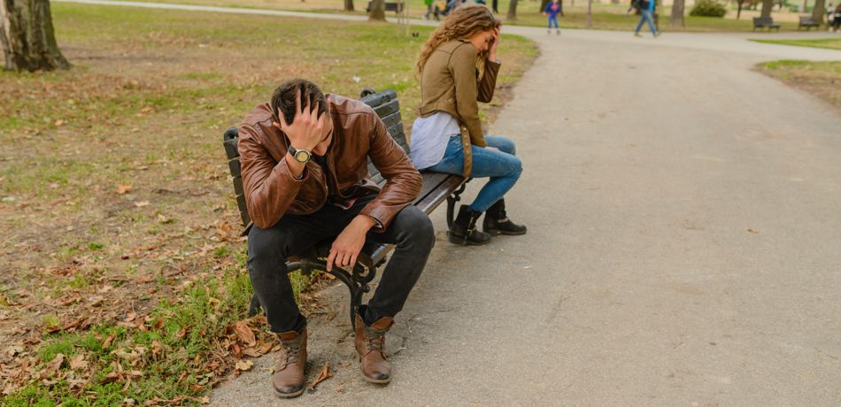Couple sitting on a bench after argument.