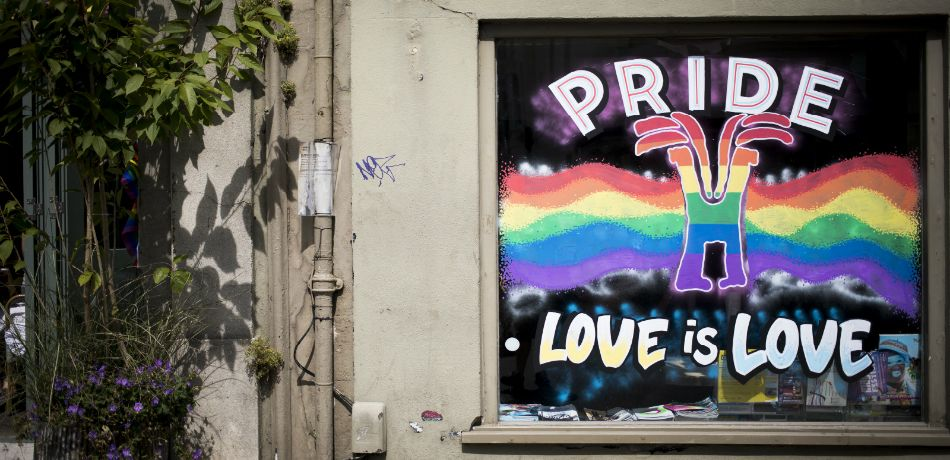 A 'Love is Love' sign is displayed on a pub window during Brighton Pride