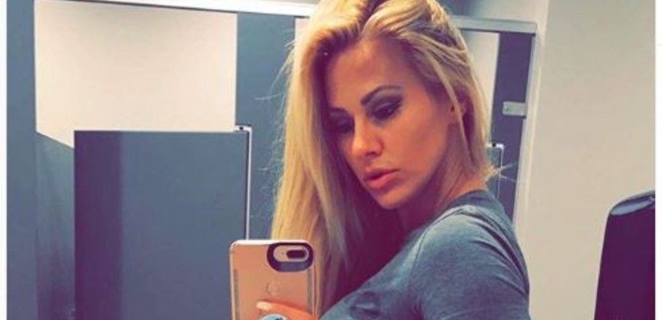 Kindly Myers poses for a selfie in gray top.