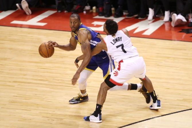 Andre Iguodala dribbles the ball against Toronto Raptors guard Kyle Lowry in the 2019 NBA Finals.