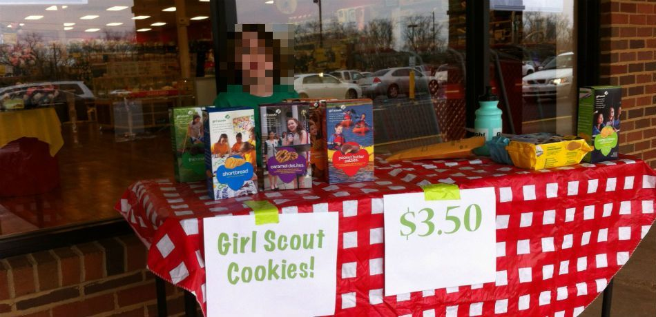 a young lady sells girl scout cookies