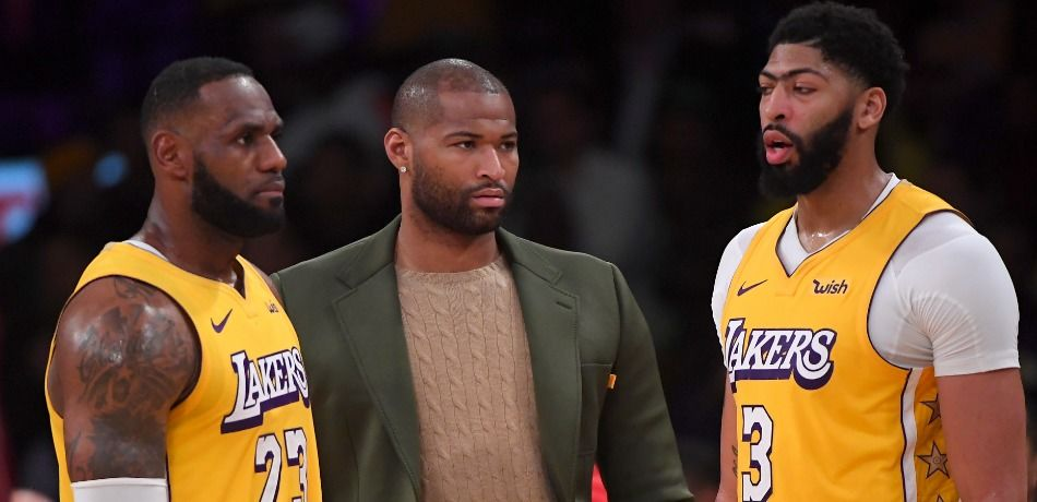 LeBron James #23 and Anthony Davis #3 talk with DeMarcus Cousins #15 of the Los Angeles Lakers on the bench during a time out in the game against the Los Angeles Clippers at Staples Center on December 25, 2019 in Los Angeles, California.