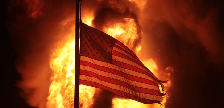 A flag flies in front of a department of corrections building after it was set ablaze during a second night of rioting on August 24, 2020 in Kenosha, Wisconsin. Rioting as well as clashes between police and protesters began Sunday night after a police officer shot Jacob Blake 7 times in the back in front of his three children.