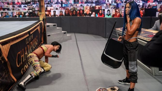 Sasha Banks stands next to Bayley, holding a steel chair