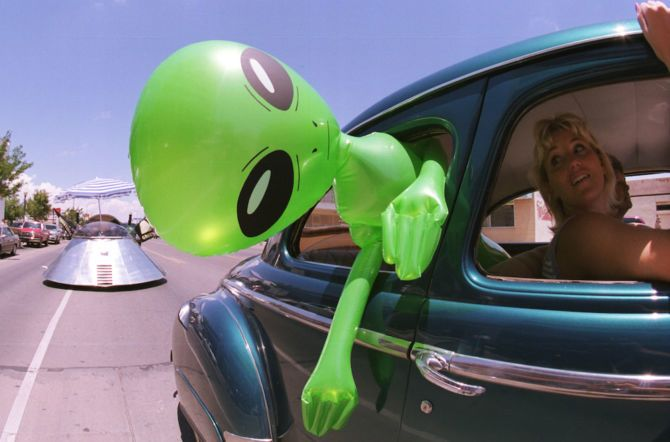 An alien doll hangs out a car window in downtown Roswell, New Mexico July 1, 2000 as part of the annual UFO Encounter, which runs through July 4, 2000.