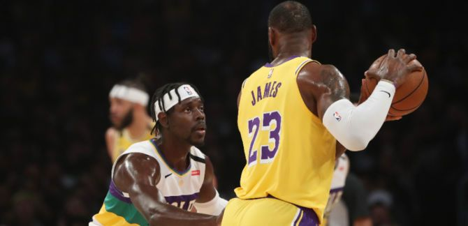 LeBron James #23 of the Los Angeles Lakers handles the ball against Jrue Holiday #11 of the New Orleans Pelicans during the first half at Staples Center on February 25, 2020 in Los Angeles, California