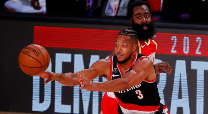 CJ McCollum of the Portland Trail Blazers passes the ball while outmaneuvering Houston Rockets guard James Harden.