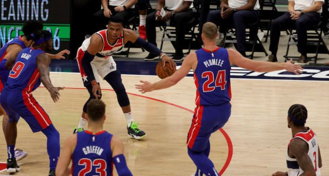 Russell Westbrook of the Washington Wizards is defended by Detroit Pistons big men Jerami Grant and Mason Plumlee.